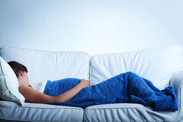 Pregnant woman in her fourth trimester resting in the couch
