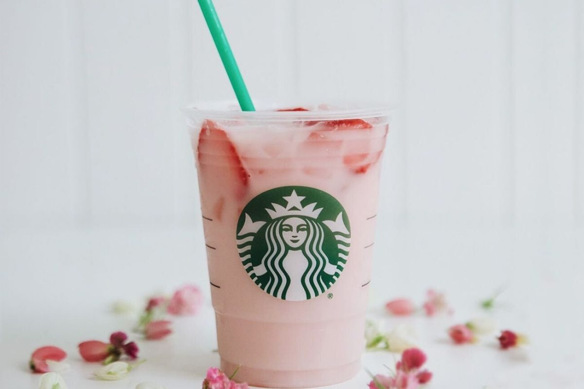 Starbucks pink drink sits on a table surrounded by flower petals